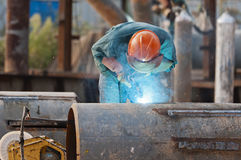Welding steel and sparks. A worker welding steel on site at a engineering site . The sparks from the arc light the gloves andw elding shield helmet Royalty Free Stock Photos