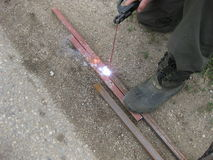 Welding of steel square pipe electric welding. The use of electric welding in the home Royalty Free Stock Photo