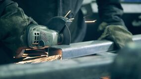 Welding technician is cutting iron beam with a saw