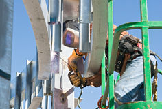 Welding in Tight Places. Welder in a lift soldering in an awkward, tight place Royalty Free Stock Photo