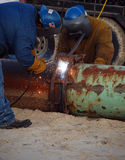 Welding two pipes together. Two men wearing safety equipment weld rusty iron pipes together Stock Images