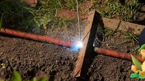 Welding work on the street. Welder cooks metall parts on the ground.