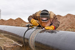 Welding works on gas pipeline. Welder mounts in the trunk pipeline electrochemical protection Stock Photos