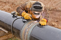 Welding works on gas pipeline. Welder mounts in the trunk pipeline electrochemical protection Royalty Free Stock Photos