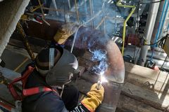 Welding works at installation of new pipeline. Welding works at installation of the new pipeline on installation of oil refining with use of the construction Royalty Free Stock Images