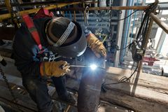 Welding works at installation of new pipeline. Welding works at installation of the new pipeline on installation of oil refining with use of the construction Stock Image