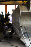 Welding in workshop. A tradesman welding an excavator bucket in a workshop with sparks Stock Image