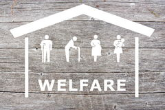 Welfare concept on wooden background. With white home and old man, disabled, pregnant and women with baby royalty free stock photos