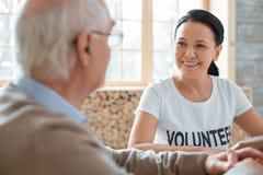 Pleasant volunteer and senior man discussing book. Welfare volunteering. Cheerful jovial volunteer smiling while speaking to senior men and looking at him stock image