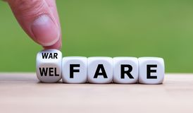 Welfare instead of warfare. Hand turns a dice and changes the word `warfare` to `welfare stock photo
