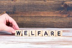 Welfare. Wooden letters on the office desk. Informative and communication background royalty free stock image