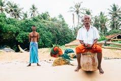 """Weligama,斯里兰卡†""""2017年12月21日:站立在海滩的两位渔夫在早晨时间的渔以后在Weligama, 免版税库存照片"""