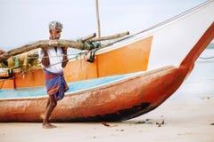 Weligama, Sri Lanka – December 21, 2017: Old fisherman pushing royalty free stock images