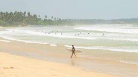 WELIGAMA, SRI LANKA - MÄRZ 2014: Ansicht des Mannverlassens ein Meer mit Surfbrett der Ausdruck Weligama bedeutet buchstäblich 's stock video footage