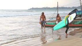 WELIGAMA, SRI LANKA - MÄRZ 2014: Boot auf dem Strand in Weligama mit den Leuten, die vorbei überschreiten Der Ausdruck Weligama b stock footage