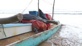 WELIGAMA, SRI LANKA - MÄRZ 2014: Boot auf dem Strand in Weligama mit den Surfern, die vorbei überschreiten Der Ausdruck Weligama  stock video footage