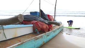 WELIGAMA, SRI LANKA - MÄRZ 2014: Boot auf dem Strand in Weligama mit den Surfern, die vorbei überschreiten Der Ausdruck Weligama  stock footage