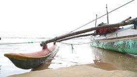 WELIGAMA, SRI LANKA - MÄRZ 2014: Boot auf dem Strand in Weligama mit einem Jungen, der vorbei überschreitet Der Ausdruck Weligama stock footage