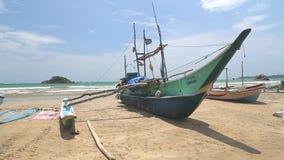 WELIGAMA, SRI LANKA - MÄRZ 2014: Boot auf einem Strand in Weligama mit den Leuten, die vorbei überschreiten Der Ausdruck Weligama stock footage