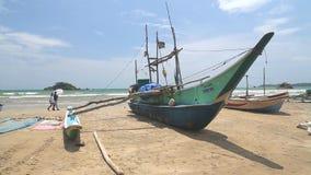 WELIGAMA, SRI LANKA - MÄRZ 2014: Boot auf einem Strand in Weligama mit den Leuten, die vorbei überschreiten Der Ausdruck Weligama stock video