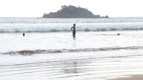 WELIGAMA, SRI LANKA - MÄRZ 2014: Die Ansicht des Ozeans in Weligama mit den lokalen Jungen, welche die Wellen genießen Das Ausdru stock video footage