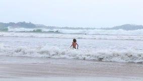 WELIGAMA, SRI LANKA - MÄRZ 2014: Die Ansicht des Ozeans in Weligama mit einem Kind, welches die Wellen genießt Der Ausdruck Welig stock footage
