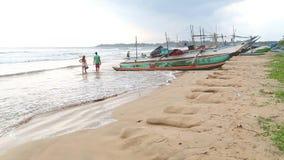 WELIGAMA, SRI LANKA - MÄRZ 2014: Die Ansicht von Booten auf dem Strand in Weligama mit den Leuten, die vorbei überschreiten Der A stock video