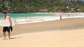WELIGAMA, SRI LANKA - 7. MÄRZ 2014: Junger Mann mit dem Brandungsbrett, das auf sandigen Strand geht Tourismus und Fischen sind d stock video