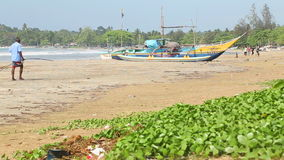 WELIGAMA, SRI LANKA - MÄRZ 2014: Kinder, die Kricket auf Strand mit Fischerboot im Vordergrund spielen stock video