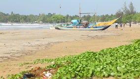 WELIGAMA, SRI LANKA - MÄRZ 2014: Kinder, die Kricket auf Strand mit Fischerboot im Vordergrund spielen stock footage