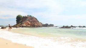 WELIGAMA, SRI LANKA - 7. MÄRZ 2014: Leute, die am sandigen Strand vor dem Standpunkt auf einem großen Felsen genießen, in dem Sie stock video