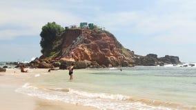 WELIGAMA, SRI LANKA - 7. MÄRZ 2014: Leute, die am sandigen Strand vor dem Standpunkt auf einem großen Felsen genießen, in dem Sie stock video footage