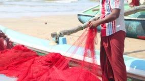WELIGAMA, SRI LANKA - MÄRZ 2014: Lokale Fischer, die Netze auf Strand nach langer Nachtfunktion sortieren Sie finden es mehr diff stock footage
