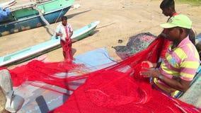 WELIGAMA, SRI LANKA - MÄRZ 2014: Lokale Fischer, die Netze auf Strand nach langer Nachtfunktion sortieren Sie finden es mehr diff stock video