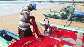 WELIGAMA, SRI LANKA - MÄRZ 2014: Schließen Sie oben vom lokalen Fischer, der Netze auf Strand nach langer Nachtfunktion sortiert  stock footage