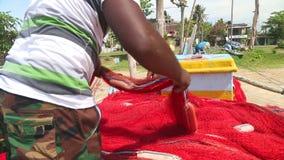 WELIGAMA, SRI LANKA - MÄRZ 2014: Schließen Sie oben vom lokalen Fischer, der Netze auf Strand nach langer Nachtfunktion sortiert  stock video footage