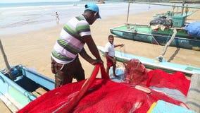 WELIGAMA, SRI LANKA - MÄRZ 2014: Schließen Sie oben vom lokalen Fischer, der Netze auf Strand nach langer Nachtfunktion sortiert  stock video