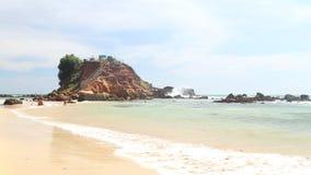 WELIGAMA, SRI LANKA - 7. MÄRZ 2014: Timelapse von den Leuten, die am sandigen Strand vor dem Standpunkt auf einem großen Felsen w stock footage