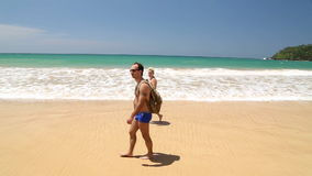WELIGAMA, SRI LANKA - 7. MÄRZ 2014: Touristische Paare, die auf sandigen Strand gehen MÄRZ 2014: Fischer, der Fischernetz auf ein stock footage