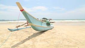 WELIGAMA, SRI LANKA - MÄRZ 2014: Traditionelles hölzernes Fischerboot auf Strand in Weligama mit den Leuten, die vorbei überschre stock video