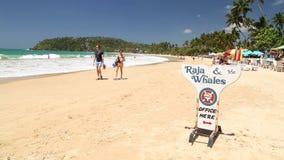 WELIGAMA, SRI LANKA - MAART 7, 2014: Jong toeristenpaar die op zandig strand lopen Het toerisme en de visserij zijn hoofdzaken tw stock footage