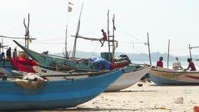WELIGAMA, SRI LANKA - MAART 2014: Lokale vissers die netten op strand na het lange nacht werken sorteren Zij vinden het meer diff stock videobeelden