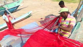 WELIGAMA, SRI LANKA - MAART 2014: Lokale vissers die netten op strand na het lange nacht werken sorteren Zij vinden het meer diff stock video