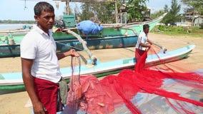 WELIGAMA, SRI LANKA - MAART 2014: Sluit omhoog van lokale vissers die netten op strand na het lange nacht werken sorteren Zij vin stock footage