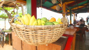 WELIGAMA, SRI LANKA - MARCH 2014: Close up view of fruit basket swinging in the wind in Weligama. Tropical fruit is available all  stock video footage