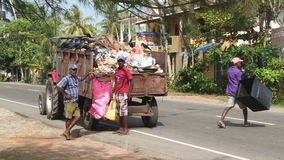 WELIGAMA, SRI LANKA - MARCH 2014: Local garbage collectors and truck in Weligama. Tourism causes a lot of waste on the coast. stock video