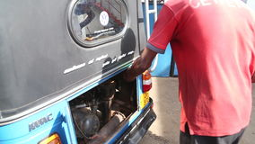 WELIGAMA, SRI LANKA - MARCH 2014: Local man putting petrol in tuktuk in Weligama. Tuktuks are an important means of transport in S stock video
