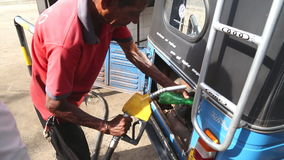 WELIGAMA, SRI LANKA - MARCH 2014: Local man putting petrol in tuktuk in Weligama. Tuktuks are an important means of transport in S stock footage