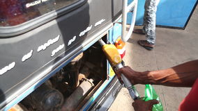 WELIGAMA, SRI LANKA - MARCH 2014: Local man putting petrol in tuktuk in Weligama. Tuktuks are an important means of transport in S stock video footage