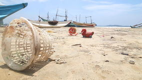 WELIGAMA, SRI LANKA - MARCH 2014: Trash washed up on shore in front of wooden fishing boast on beach. stock footage